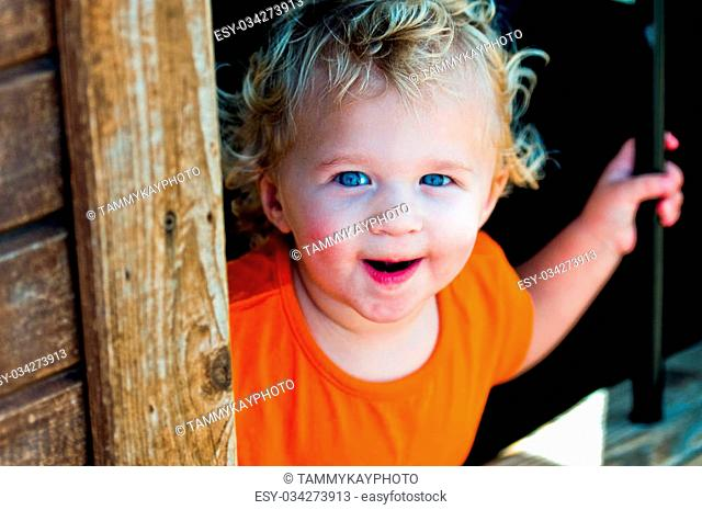 Close up of curly blonde haired toddler girl behind bars at a pumpkin festival