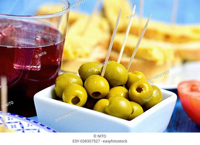 closeup of a glass with tinto de verano, a bowl with olives and a plate with tortilla de patatas, spanish omelet, served as tapas on sliced bread in the...