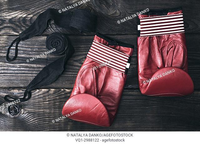 red leather boxing gloves and a black elastic bandage on a brown wooden background, vintage toning