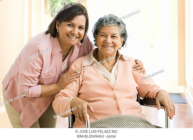 Senior Hispanic woman and adult daughter hugging