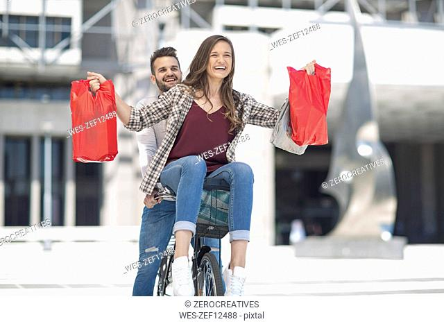 Happy young couple having fun in the city riding bicycle with shopping bags