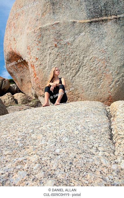 Young woman practicing yoga taking a break on beach boulder, Cape Town, Western Cape, South Africa
