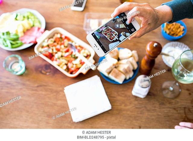 Woman photographing appetizers on table with cell phone