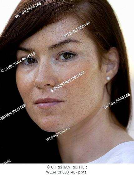 Portrait of woman with brown hair and freckles, close-up