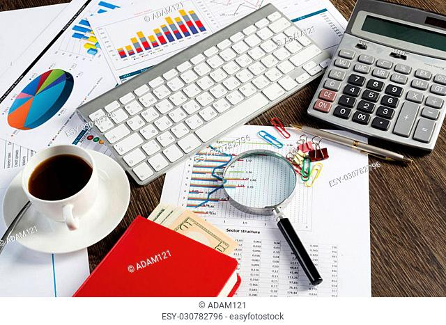 Close up of keyboard documents and coffee on office table