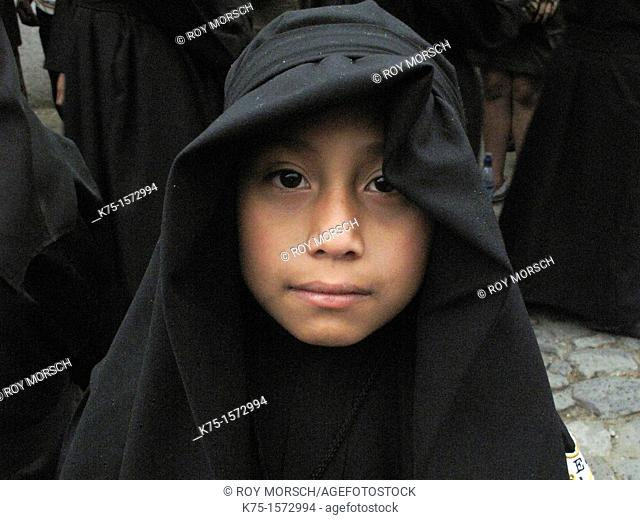 Young boy in black robe for procession during Holy Week