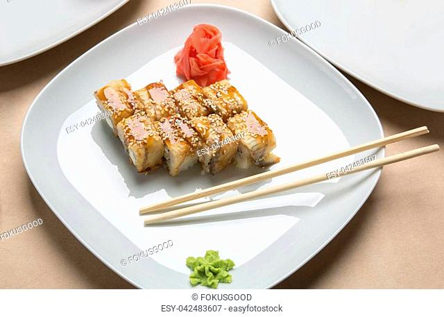 delicious rolls with eel and ginger on a white plate in a restaurant