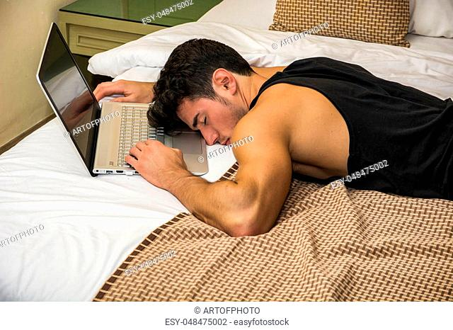 Close Up of Tired Young Man with Dark Hair Sleeping on Floor Next to Laptop Computer with Hand on Keyboard