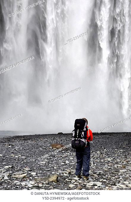single female tourist with backpack in front of Skogafoss waterfall, Iceland
