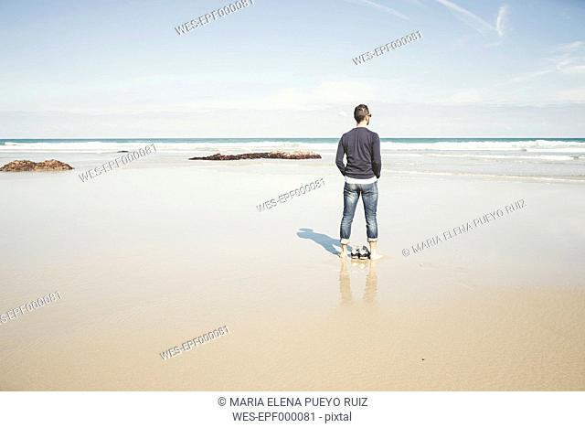 Spain, Ribadeo, Young man on Las Catedrales Beach on a spring day