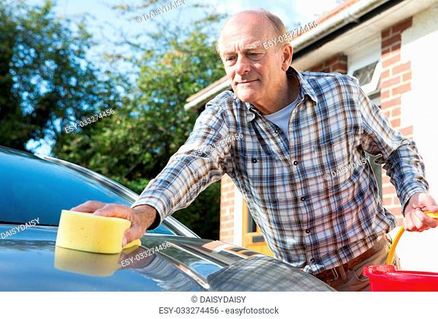 Senior Man Washing Car With Sponge