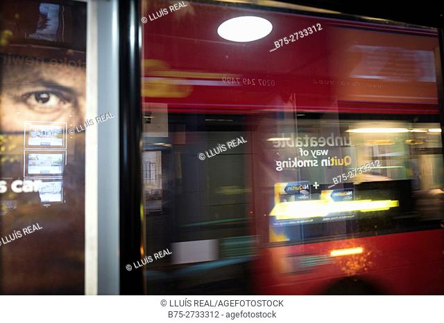 Bus in motion, eye from billboard advertising looking at camera. London, England
