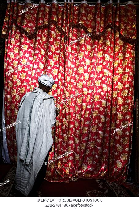 Ethiopia, Amhara Region, Lalibela, orthodox priest praying with a bible in front of a curtain
