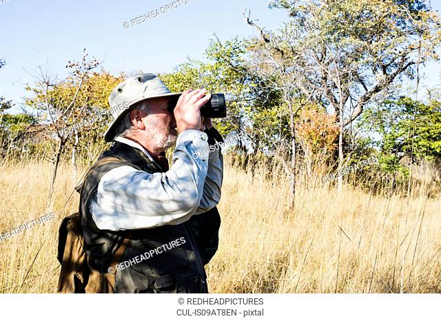 Senior man looking through binoculars on safari, Kafue National Park, Zambia