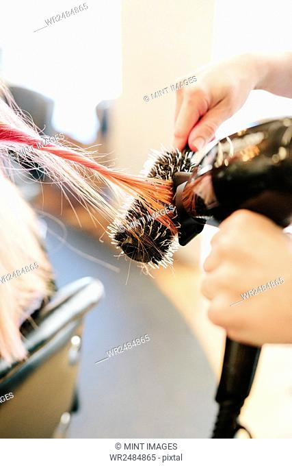 A hair stylist blow-drying a client's long straight pink hair using a round bristle brush