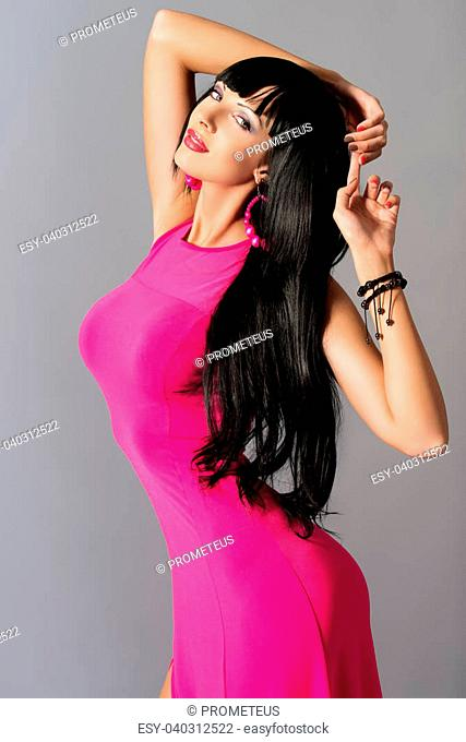 Fashion photo of a beautiful model in long summer dress and sunglasses