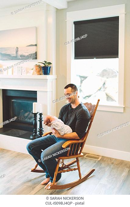 Father sitting in rocking chair holding newborn baby boy