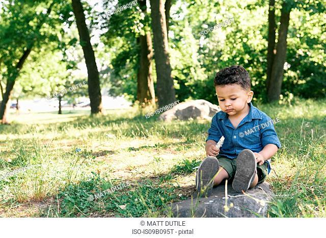 Male toddler sitting eating sweet bar in Pelham Bay Park, Bronx, New York, USA