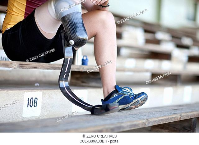 Sprinter sitting with prosthetic leg on