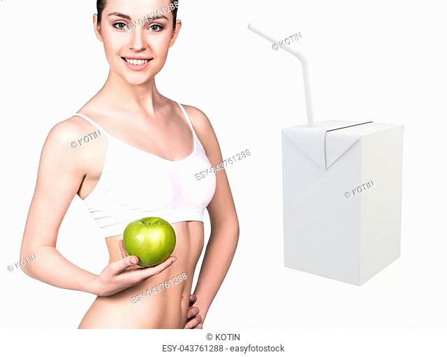 Happy young woman holds an apple near juice box template. Healthy eating concept