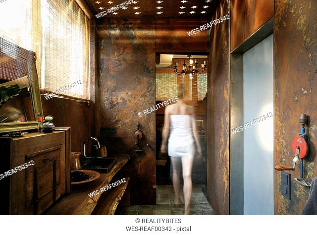 Back view of woman walking in bathroom with corten steel wall cladding and ceiling light effects