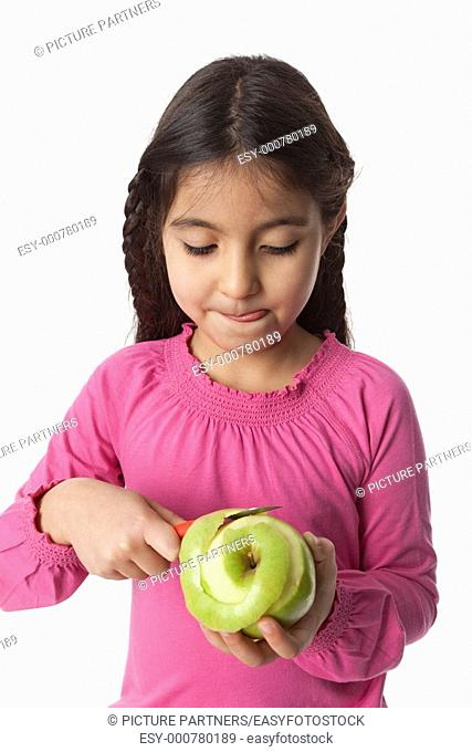 Little girl peeling an apple with a knife on white background