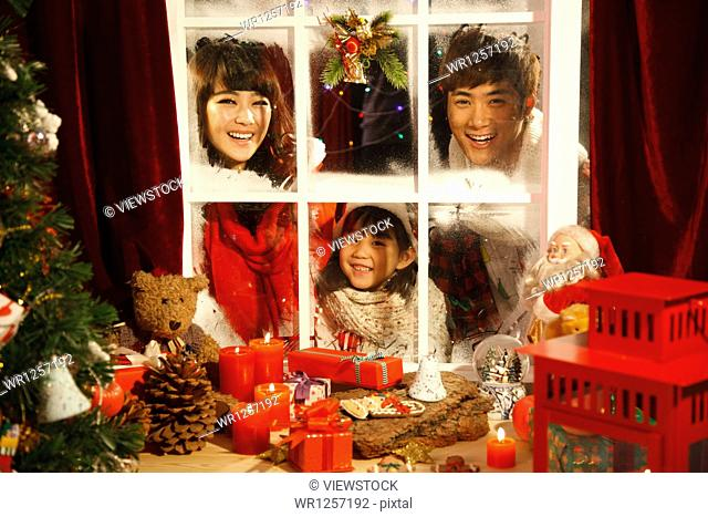 Family looking at Christmas gifts through window