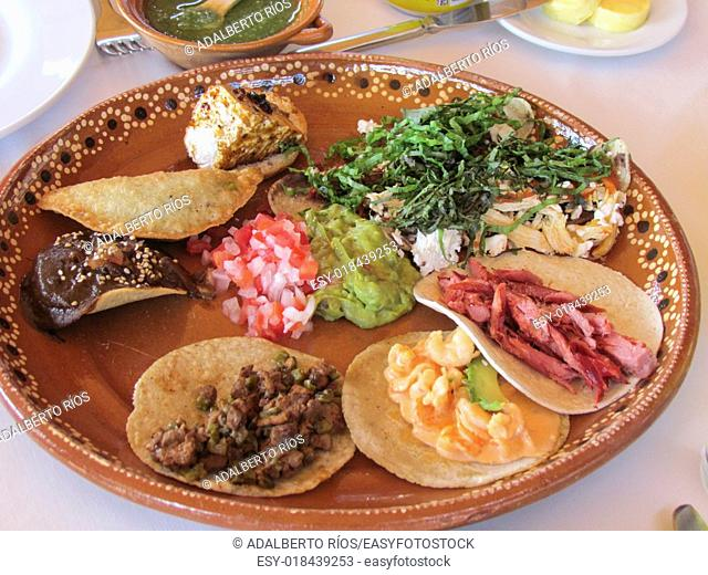 Mexican dishes with huitlacoche corn fungus quesadilla with cheese, beans and squash blossoms. . Taquitos tip steak with nopales