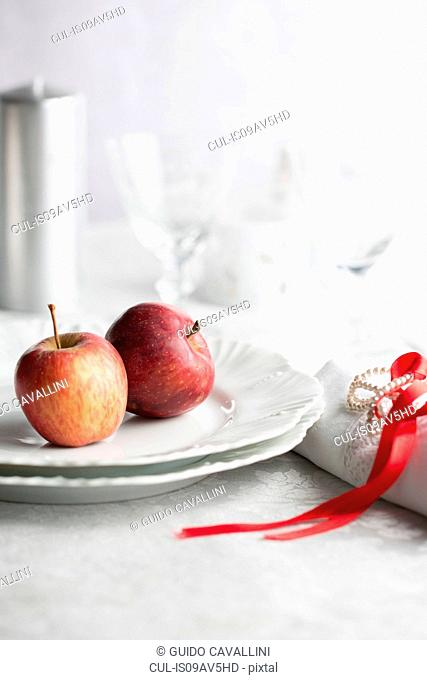 Red apples on plate, napkin tied with red ribbon