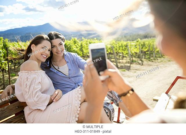 Woman with camera phone photographing friends in sunny vineyard