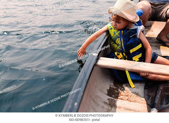 Girl touching water from rowing boat on lake