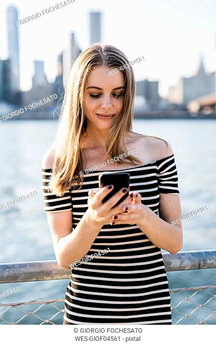 USA, New York, Brooklyn, young woman looking at smartphone