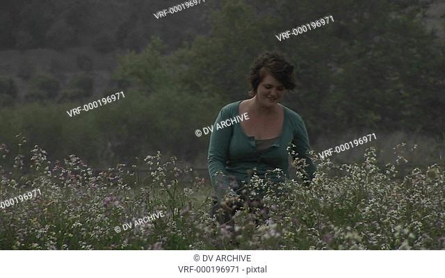 A woman walks through wildflowers