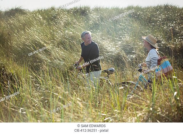 Mature couple walking bicycles in sunny beach grass