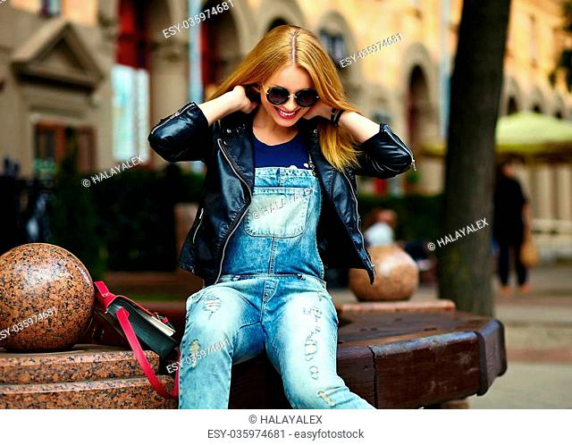 portrait of cute funny modern sexy urban young stylish smiling woman girl model in bright modern cloth outdoors sitting in the park in jeans on a bench in...