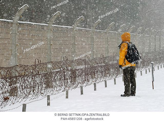 A visitor views the former perimeter fence at the memorial site of the concentration camp Sachsenhausen in Oranienburg, Germany, 27 January 2014