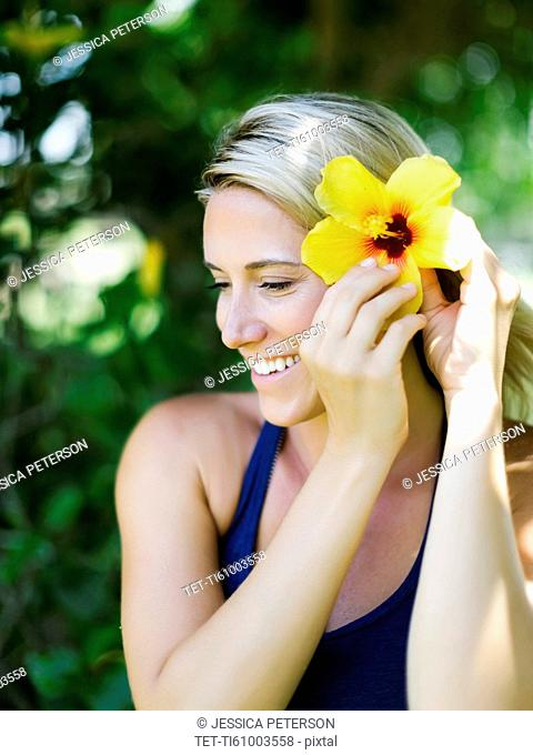 Blonde beautiful woman decorates hair with flower