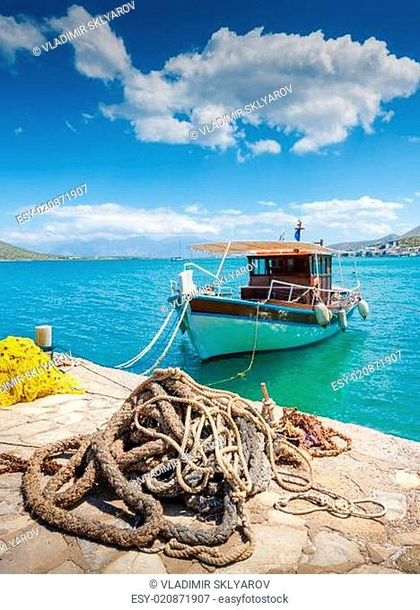 Fishing Boat off the coast of Crete with marine rope and fishing net in the foreground