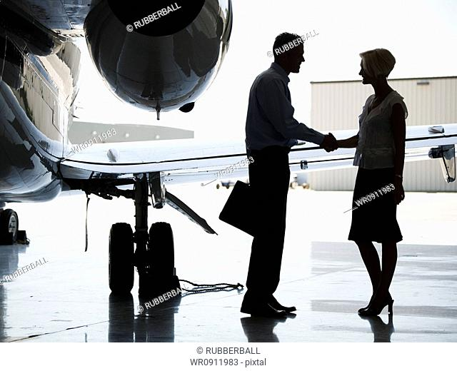 Profile of a businessman and a businesswoman shaking hands by an airplane