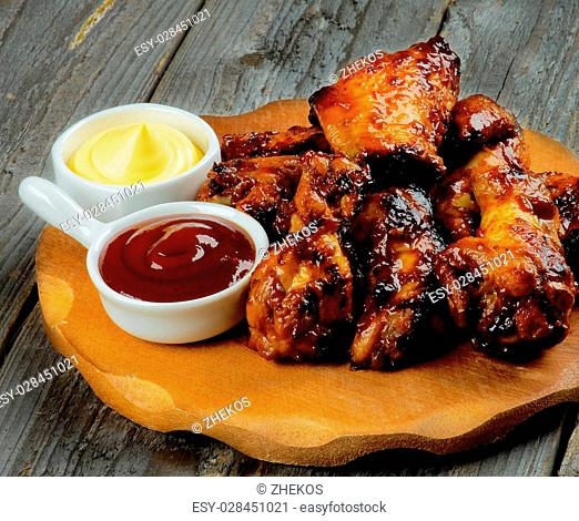 Roasted Chicken Legs and Wings Barbecue with Two Sauces on Wooden Plate closeup on Rustic Wooden background