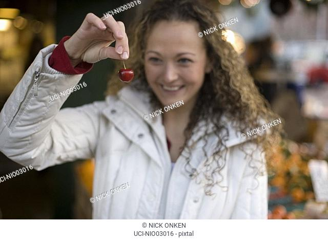 Young woman holding a cherry
