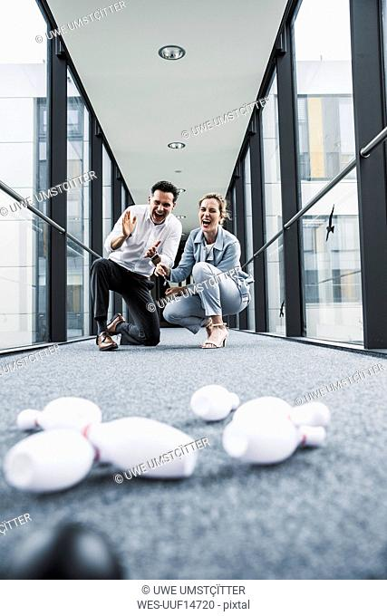 Cheering businessman and businessman in office passageway with fallen pins
