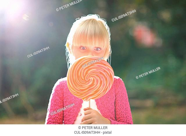 Portrait of girl with lollipop in front of her face in garden