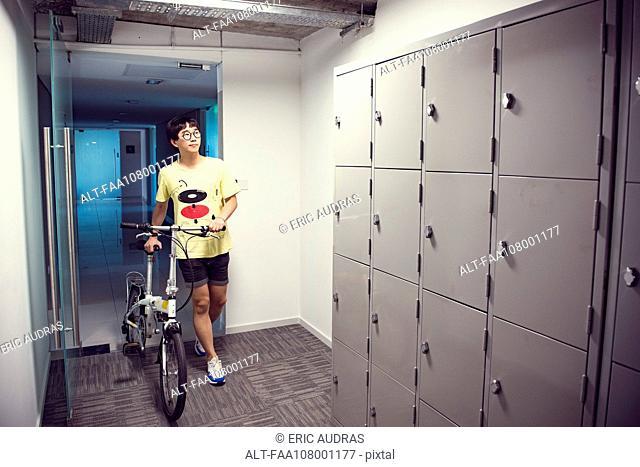 Man walking toward indoor lockers with bicycle