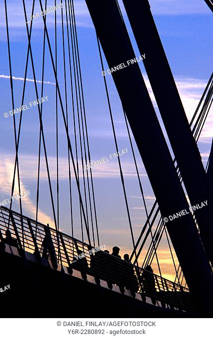 Pedestrians crossing Hungerford Footbridge across the River Thames in the heart of London, England, at dusk