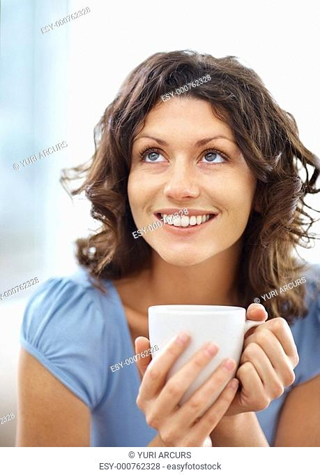 Closeup of a beautiful smiling young lady holding coffee cup and looking up