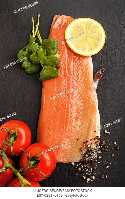 raw trout fillet with slice lemon, wet tomato crushed peppercorn and fresh coriander on slate