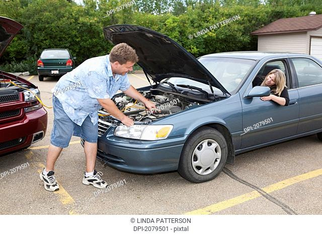 A man helps boost the car battery of a woman's car in a parking lot, edmonton alberta canada