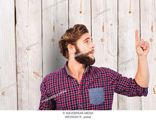 Male hipster pointing upwards against wooden wall