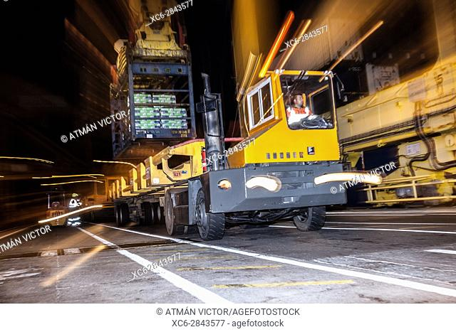 Stationary yellow cargo truck being loaded with a blue container of goods in Santa Cruz de Tenerife dock at night